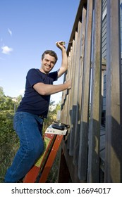 Happy man on a ladder repairing siding of a house with a screwdriver. Vertically framed photo.