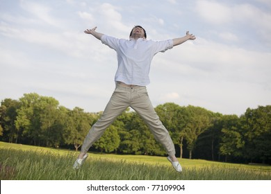 happy man on meadow jumping in the air