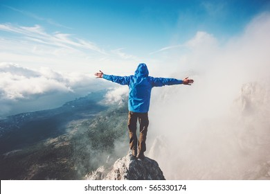 Happy Man on mountain summit enjoying aerial view hands raised over clouds Travel Lifestyle success concept adventure active vacations outdoor freedom emotions