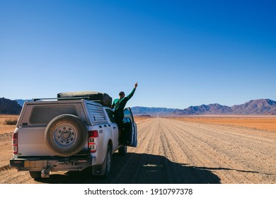 happy man on top of an all-terrain vehicle driving through gravel landscapes in namibia