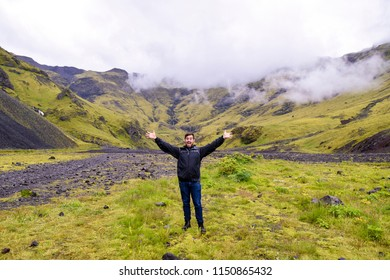 Happy man on vacation.  Hiking in Iceland with arms outstretched.  On path to Seljavallalaug Pool on the South Coast.