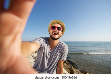 Happy man on vacation laughing at the beach taking selfie