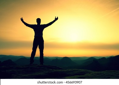 Happy man with open raised arms Gesture of triumph. Satisfy hiker  silhouette on sandstone cliff watching down to landscape.