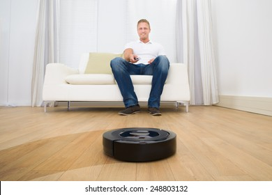 Happy Man Operating Robotic Vacuum Cleaner With Remote Control At Home