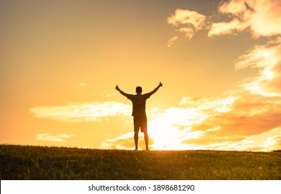 Happy man outdoors feeling rejuvenated with arms outstretched up to the sunset sky.