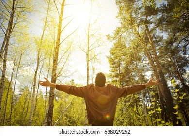 Happy man in a park in spring or summer forest, happiness, hope and vitality. The man lifted the cookies to the top, reaching for the sky and the sun enjoying life outdoors outdoors. Absolute freedom