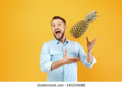 Happy man with pineapple on color background
