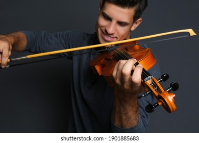 Happy man playing violin on black background, focus on hand