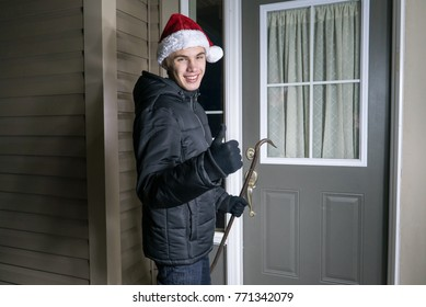Happy man preparing to rob a house holding a crow bar while wearing a santa hat.