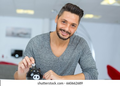 happy man putting coin in piggy bank