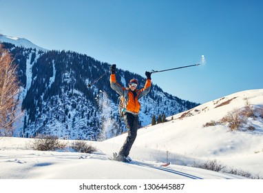 Happy Man raising his hand and skiing on fresh powder snow at forest in the Tien Shan Mountains, Kazakhstan