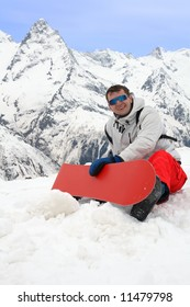 Happy man with red snowboard in mountains