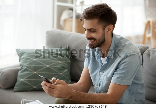 Happy man relax on couch at home chatting with friends on smartphone, excited millennial male writing message on cell to girlfriend, smiling guy using mobile phone texting or playing app games