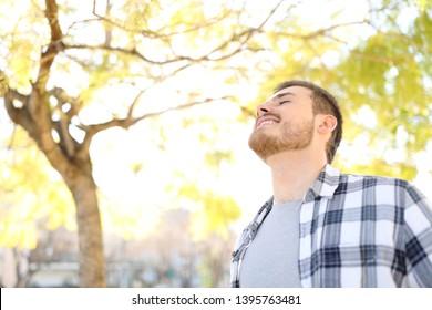Happy man relaxing breathing deep fresh air standing in a park