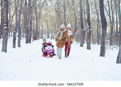 Happy man riding kids on sledge in winter park