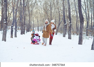 Happy man riding kids on sledge while spending time in winter park