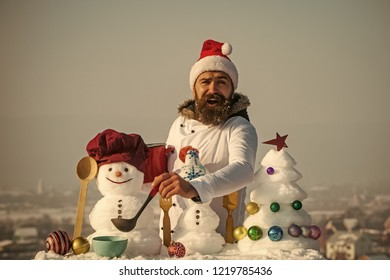 Happy man in santa hat ladling soup on winter day. Christmas and new year holidays food. Hipster with ladle in white uniform. Cooking and diet concept. Cook, snowmen and snow xmas tree on blue sky.