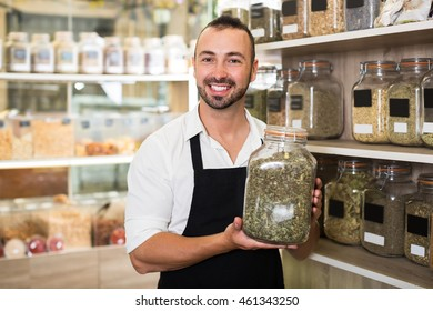 Happy man seller holding glass can with dried herbs in organic shop