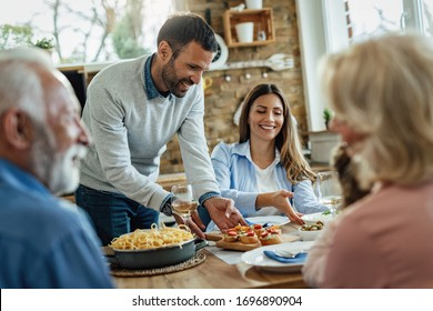 Happy man serving appetizer while having lunch with his family in dining room.