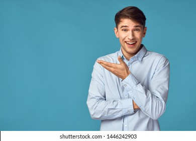 Happy man in shirt shows hand to side on blue isolated background