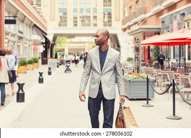 Happy man with shopping bags walking on a street