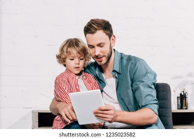 happy man showing digital tablet to little son at home