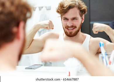 Happy man showing his biceps in front of mirror