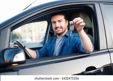 Happy man showing his new car key