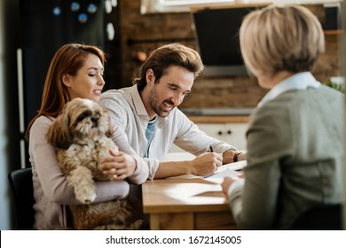 Happy man signing a contract while being with his wife on a meeting with financial advisor.