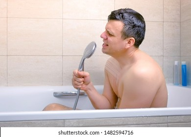 Happy man is singing with shower as a microphone while he is washing in bathtub. Side view.