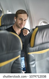 Happy man sits in the airplane next to the window and looks into the camera with a smile. He wears a black T-shirt, blue jeans and wireless headphones. Closeup. Vertical.