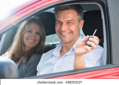 Happy Man Sitting Inside The Car With His Wife Showing Car Key