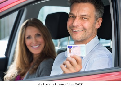 Happy Man Sitting Inside The Car With His Wife Showing Driving License