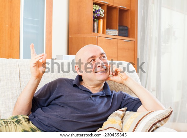 Happy man sitting on a couch in living room