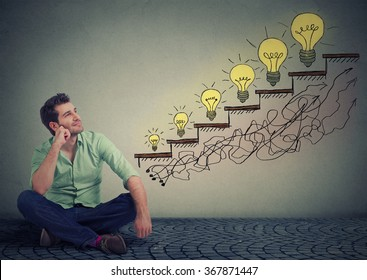 Happy man sitting on a floor in his office dreaming of business education success, promotion, company growth isolated gray wall texture background. Handsome guy looking up at growing up light bulbs