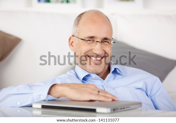 Happy man sitting on the floor and holding a laptop on table