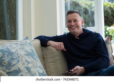 Happy man sitting on sofa in living room