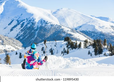 Happy man sitting on top of Alps, resting after skiing against wonderful winter mountains background