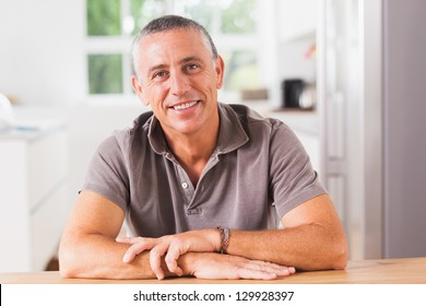 Happy man sitting at table in kitchen