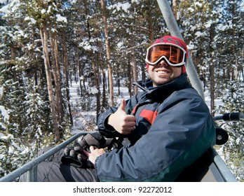 Happy man skier lift on chairlift in forest