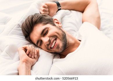 Happy man sleeping in bedroom