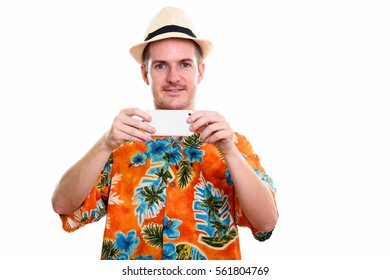 Happy man smiling while taking picture with mobile phone and looking at camera