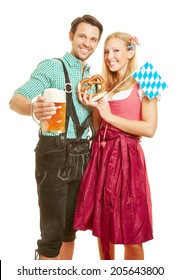 Happy man and smiling woman with beer and pretzel at Oktoberfest in Bavaria