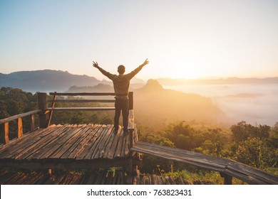 Happy of man standing alone with arms raised up  during beautiful sunrise at the morning.Enjoying with nature