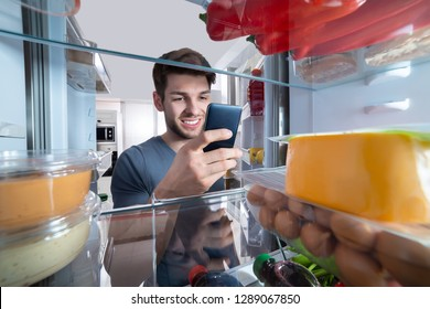 Happy Man Standing In Front Of Refrigerator Using Mobilephone In Kitchen