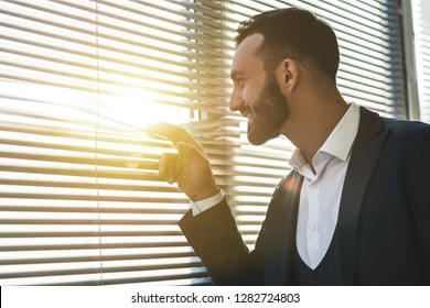 The happy man standing near the window with jalousie