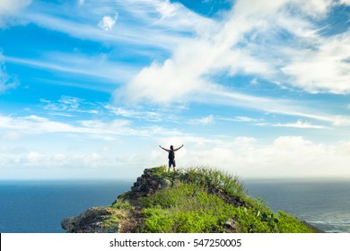 Happy man standing on the peak of the mountain, over looking the ocean. Success, winner, happiness.