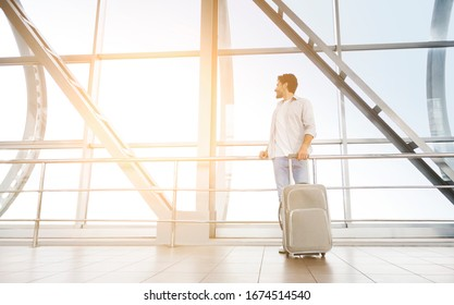 Happy man standing with suitcase near window in airport terminal, enjoying sunset view, free space
