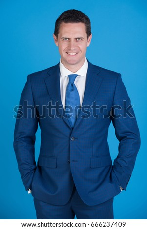 26e45bc99 Happy man, successful businessman or confident boss smiling with hands in  pockets in elegant navy formal suit, white shirt and tie on blue background.