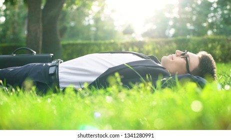 Happy man in suit lying on grass and enjoying sunny day, harmony with nature